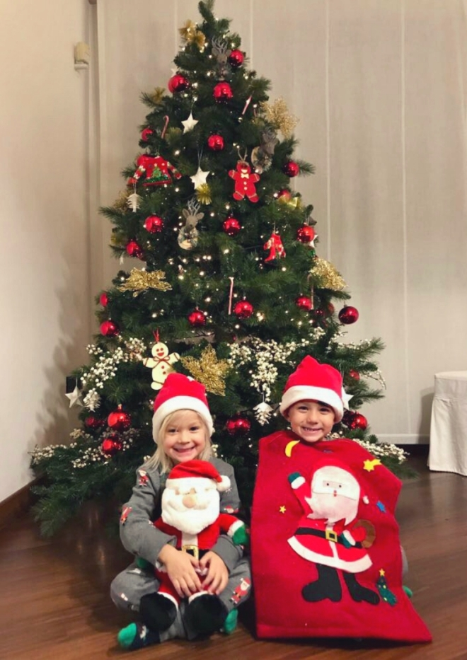 Twins sitting under a christmas tree